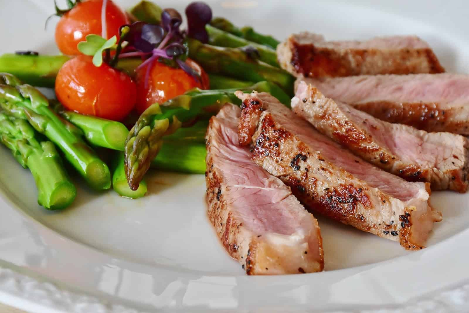 Steak, asparagus and tomatoes on plate.