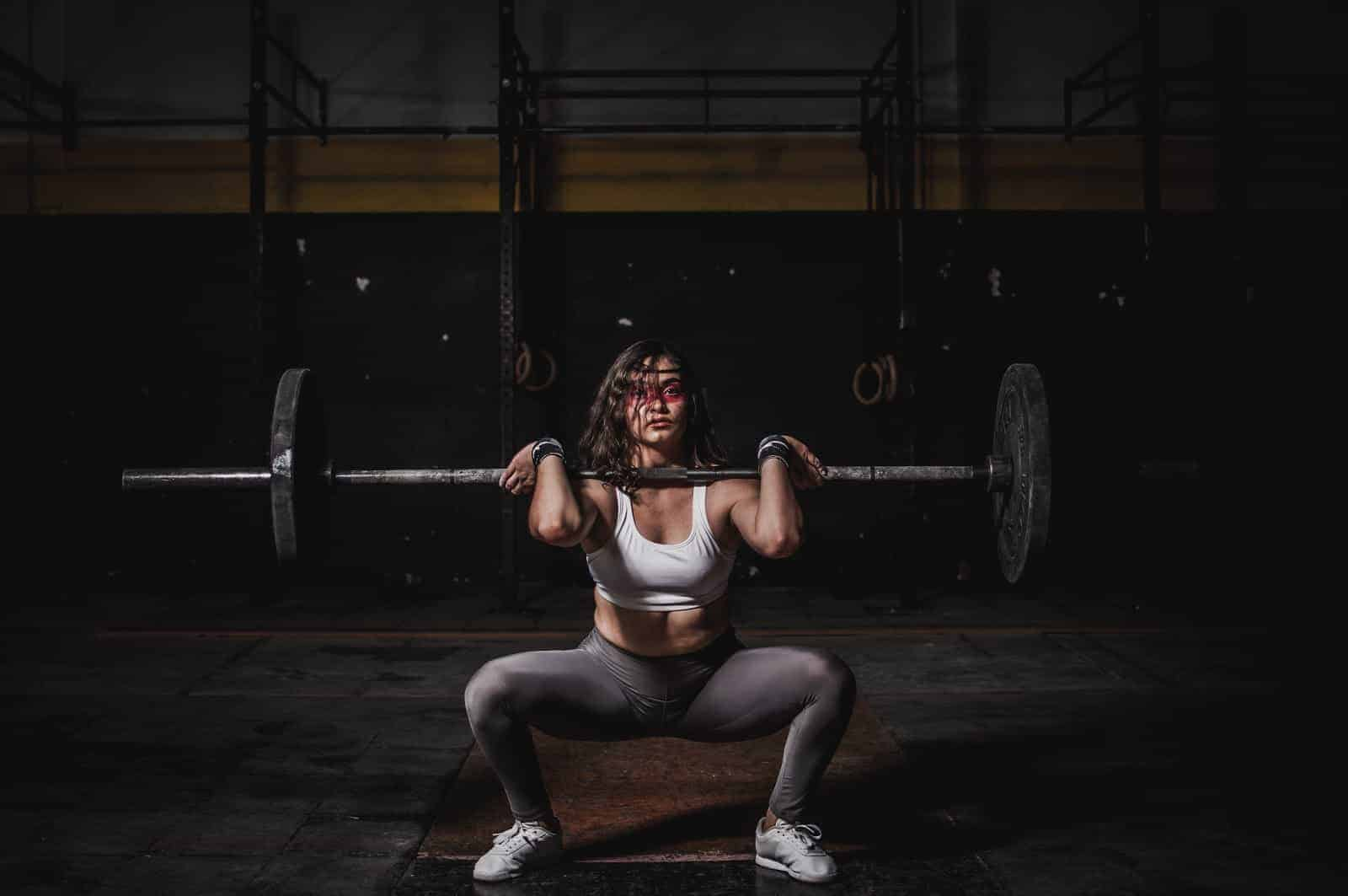 Strong woman squatting a barbell in connection with a discussion of whether intermittent fasting is for everyone.