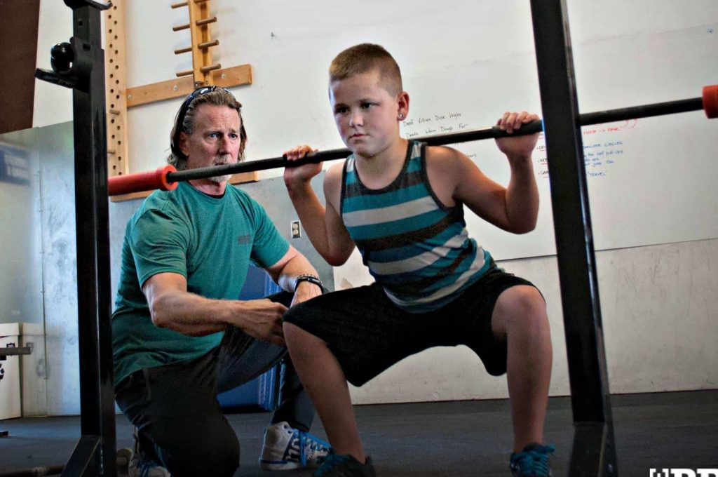Kid with a barbell squatting