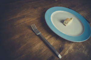 Plate with a small morsel of food to highlight high calorie restriction diets