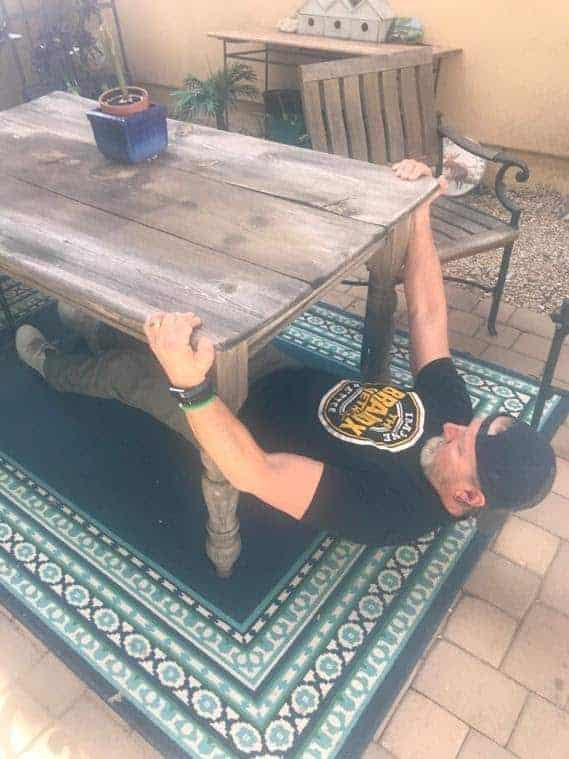 Jeff Martin doing an elevated push up under a table.