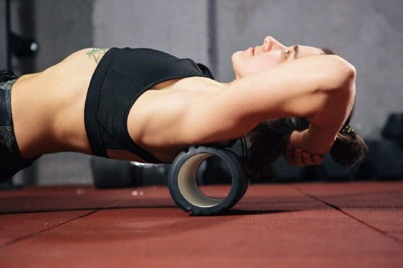 Woman rolling on a foam roller to emphasize the importance of mobilizing in order to build muscle at any age