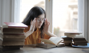 Woman holding her temples reading a book to demonstrate the effects of too much caffeine