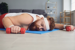 Man lying on an exercise mat holding weights, asleep, to illustrate fatigue from stress and high cortisol