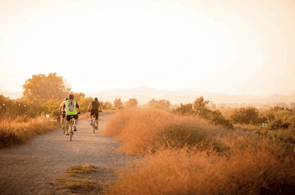 Three people biking into the sunset to demonstrate how hydration improves physical performance