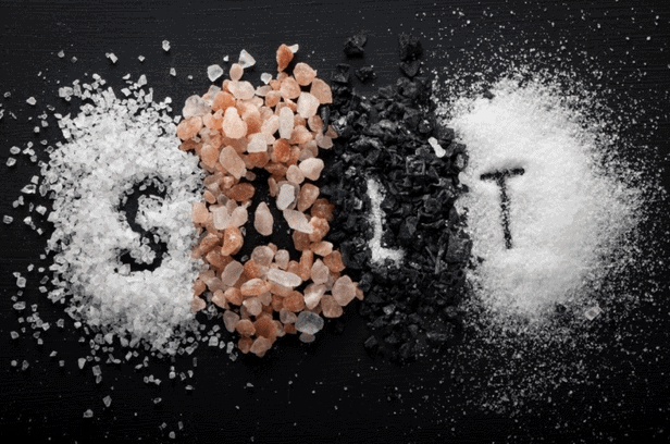 Piles of salt with the word salt written in salt to represent the importance of salt in your diet