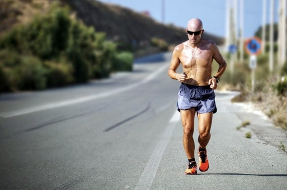 Man running on the side of the road on a hot day to illustrate the need for electrolyte supplements