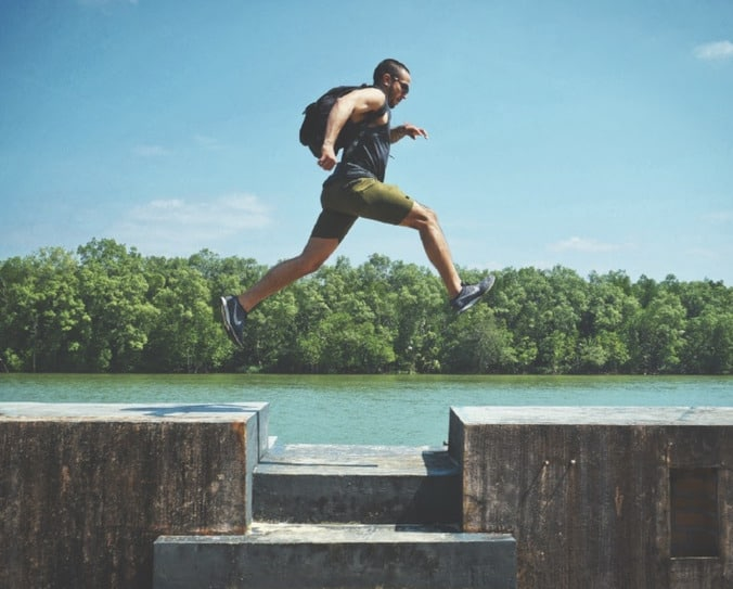 Man jumping over an outdoor obstacle to demonstrate how to accomplish your fitness goals
