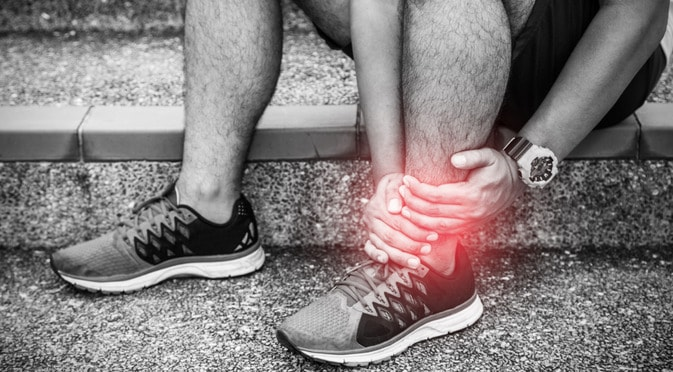 Man holding his red injured ankle to demonstrate the relationship between genetics and recovery